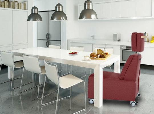 """Durch die komplett entfernbaren Armlehnen wird der Nutzen noch flexibler: Der Sessel kann direkt an einen Tisch gerollt werden. Dadurch nimmt der Betroffene problemlos noch intensiver am Tagesablauf teil ohne seinen ergonomischen """"Lieblingsplatz"""" verlassen zu müssen."""
