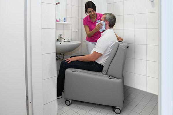 Pflegesessel / Aufstehsessel: Die entfernten Armlehnen am Sessel vereinfachen die Körperpflege. Durch die Rollen ist er auch in engen Räumen nutzbar.