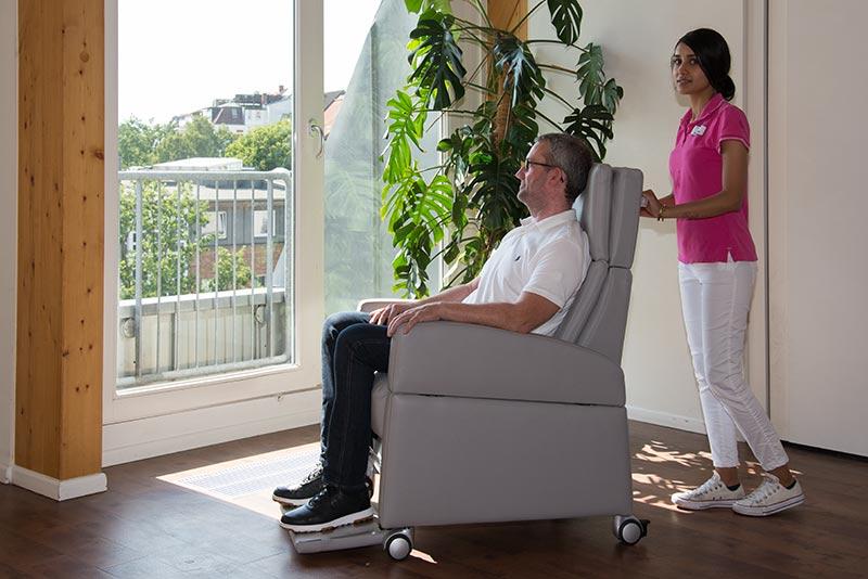 Pflegesessel als Hilfsmittel für die Pflegekräfte: Pflegerin rollt den ReHa-Sessel im Seniorenheim. Einfaches Bewegen des Sessels dank der Rollen. Erleichterung in der Pflege