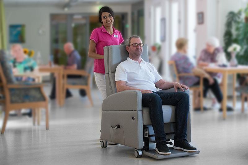 Senior wird im Aufstehsessel / Pflegesessel VIANDOpflege® mit-Rollen, in Senioren-Einrichtung zum Essen gebracht