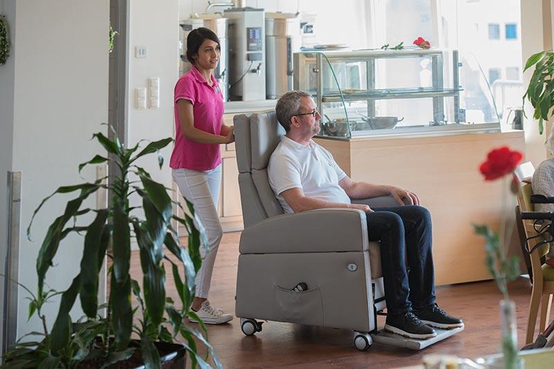 Mit dem Ruhesessel mit Aufstehilfe vom Zimmer an den Esstisch, der Pflegesessel mit Rollen bietet Mobilität