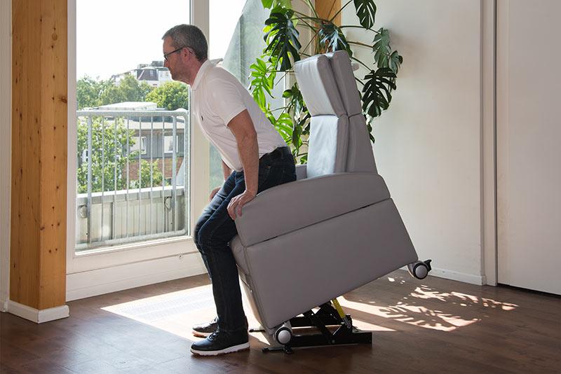 Mann nutzt die Aufstehhilfe am Aufstehsessel: Diese Aufstehhilfe ist auch eine Erleichterung im Pflegealltag und für die Pflegehelfer
