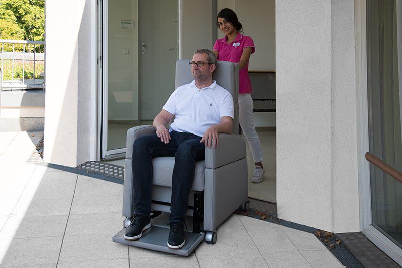 Pfleger rollt Senior im Aufstehsessel mit Rollen auf die Terrasse. Der Aufstehsessel ermöglichen eine einfache Umplatzierung des Betroffenen mit dem Pflegestuhl innerhalb der Wohnung / Einrichtung oder auf die Terrasse.
