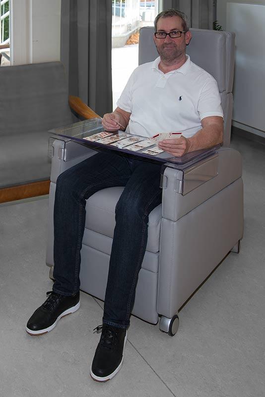 Betroffener sitzt auf dem Pflegesessel / ReHasesselVIANDOpflege® und nutzt den aufsteckbarer Therapie-Tisch