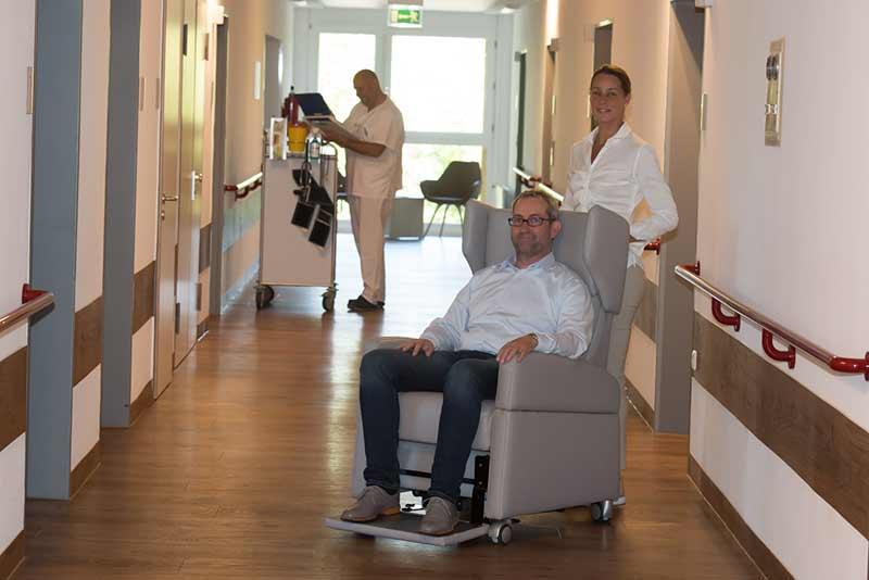 """Reha-Pflegesessel mit Rollen für Patienten-Mobilität in Klink (""""Klinik Möbel"""")."""